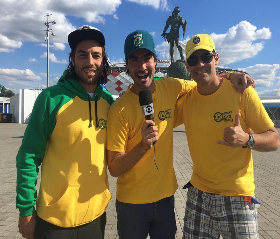 Membros do MVA em frente de estádio na copa da Rússia pousando com microfone da Globo na mão