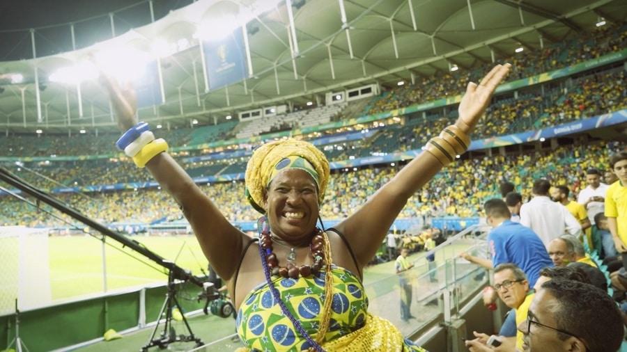 Torcedora brasileira pousa sorridente com os braços para cima na arquibancada