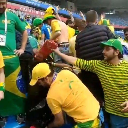 Torcedores da Seleção Brasileira recolhem lixo em estádio após jogo da seleção.