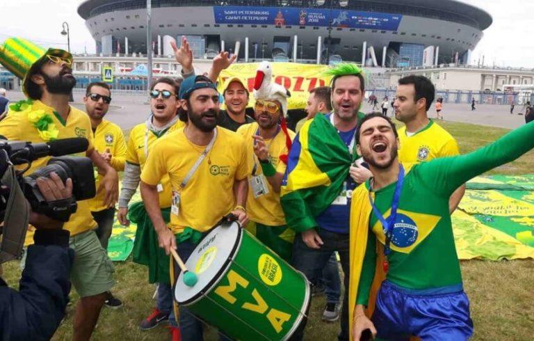Membros do MVA cantando para uma transmissão de TV na frente de um estádio na copa da Rússia