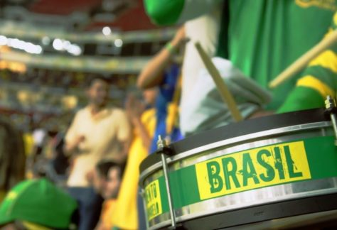 Close de uma caixa da bateria verde com um adesivo amarelo escrito Brasil com torcida desfocada ao fundo